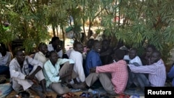 Internally displaced men sit inside a United Nations Missions in Sudan (UNMIS) compound in Juba December 19, 2013. South Sudanese government troops battled to regain control of a flashpoint town and sent forces to quell fighting in a vital oil producing a