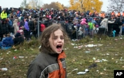 FILE - A girl cries as hundreds of migrants wait to cross into Austria from Sentilj, Slovenia, Oct. 29, 2015.
