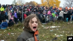 A girl cries as hundreds of migrants wait to cross into Austria from Sentilj, Slovenia, Oct. 29, 2015. In the chaos of migration, children are especially vulnerable to predators. In Germany, a suspect in the death of one boy has confessed to a second slay