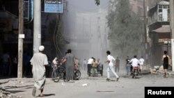 Cư dân bỏ chạy vì pháo kích trên đường phố ở thị trấn Aleppo của thành phố al-Shaar, ngày 16/9/2012