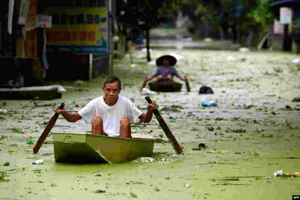 People take boats through floodwaters in Hanoi's suburban Chuong My district, Vietnam.