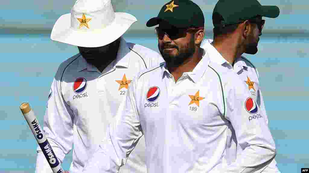 پاکستانی کپتان اظہر علی مہمان ٹیم کو شکست دینے کے بعد ہاتھوں میں وکٹ تھامے گراؤنڈ سے پویلین لوٹ رہے ہیں۔