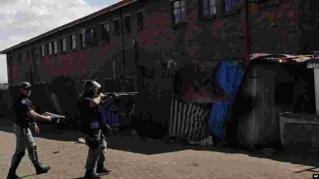 Polisi wa Afrika Kusini wakiwa na bunduki wachukau hatua kutawanya wapinga wageni nje ya mtaa wa mashariki wa Actonville, Johanesburg.
