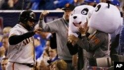 Pablo Sandoval es celebrado por dos aficionados con máscaras de Kung Fu Panda, el apodo con el que se le conoce, durante el séptimo juego de la Serie Mundial contra Kansas.
