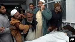 Pakistanis mourn next to the body of their relative killed in a suicide bombing, at a local hospital in Peshawar, Pakistan, Saturday, Dec. 22, 2012.