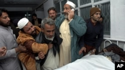 巴基斯坦人12月22日在白沙瓦一家医院里哀悼他们在炸弹袭击中死去的亲人