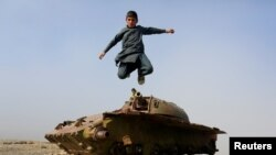 An Afghan boy jumps from the remains of a Soviet-era tank on the outskirts of Jalalabad, Afghanistan, Feb. 15, 2019.