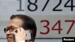ຊາຍຄົນນຶ່ງ ກຳລັງໃຊ້ໂທລະສັບ smartphone ຍ່າງຜ່ານ ກະດານອີເລັກໂທຣນິກ ສະແດງລາຄາຮຸ້ນ Nikkei ຂອງຍີ່ປຸ່ນ (27 ສິງຫາ 2015).