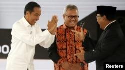 Capres 01 Joko Widodo dan Capres 02 Prabowo Subianto saling memberi hormat disaksikan Ketua KPU Arief Budiman pada acara debat di Jakarta, Sabtu (30/3).