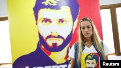 FILE - Lilian Tintori, wife of jailed Venezuelan opposition leader Leopoldo Lopez, stands near a poster depicting him at the Popular Will party's office in Caracas, Venezuela, Jan. 18, 2017.