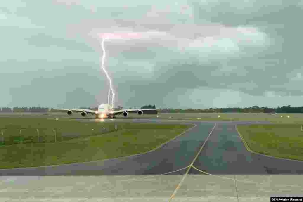 A lightning strikes near an Emirates A380 plane at Christchurch Airport, New Zealand in this still image obtained from a social media video.