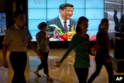 People walk past a large videoscreen showing Chinese President Xi Jinping during his trip to the United States from Chinese state broadcaster CCTV in an office building in Beijing, Sept. 25, 2015.