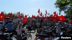 Workers wave Vietnamese national flags during an anti-China protest at a Chinese-owned shoe factory in Vietnam's northern Thai Binh province May 14, 2014.