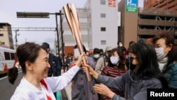 FILE PHOTO: Spectators try to touch the torch carried by torchbearer Junko Ito, after her run during the Tokyo 2020 Olympic torch relay on the second day of the relay in Fukushima, Japan March 26, 2021. REUTERS/Issei Kato/File Photo