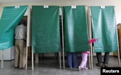 FILE - A child gestures during 2012 municipal elections in Valparaiso, Chile. The country reportedly works hard to enfranchise voters.
