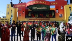 Kurdish people dance during the Nowruz celebrations in southeastern Turkish city of Diyarbakir, March 21, 2014.