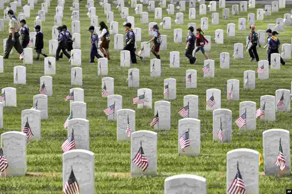 Boy Scouts and Girl Scouts walk between grave stones after helping place flags at the Los Angeles National Cemetery, May 26, 2018.