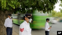 Polusi India mengenakan masker sambil mengatur lalu lintas di New Delhi, India.