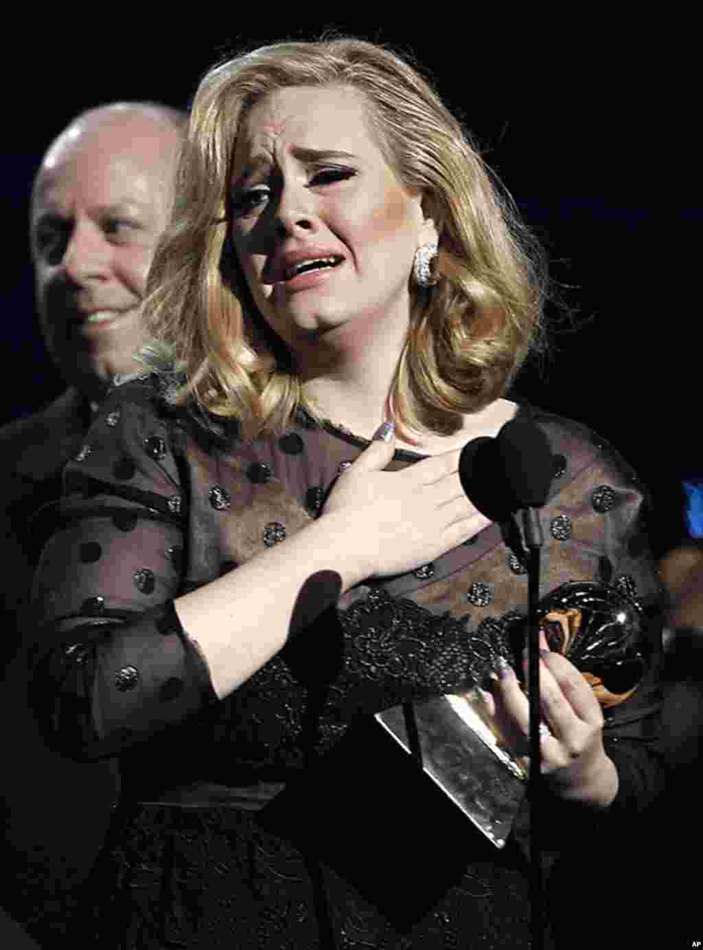"""Adele accepts the award for record of the year for """"Rolling in the Deep"""" during the 54th annual Grammy Awards in Los Angeles, February 12, 2012. (AP Photo/Matt Sayles)"""