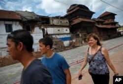 Khách du lịch đi bộ gần các tòa nhà ở Kathmandu bị hư hại sau trận động đất kinh hoàng.