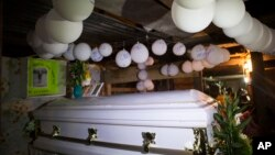 Balloons hang over the coffin that contain the remains of 7-year-old Jakelin Caal Maquin during a memorial service in her grandparent's home in San Antonio Secortez, Guatemala, Monday, Dec. 24, 2018.