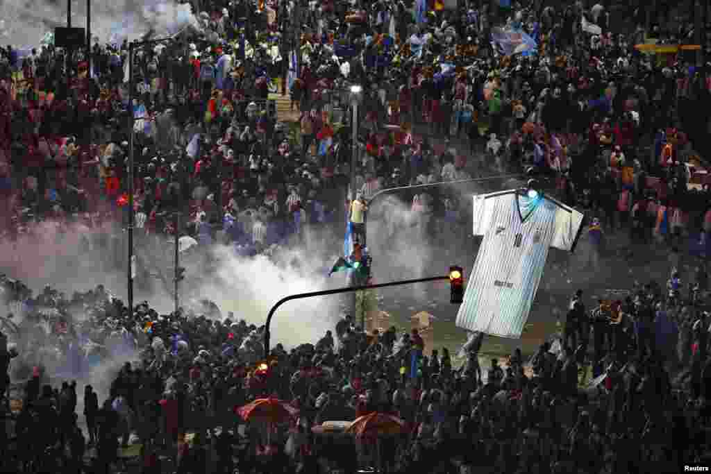Argentina's fans run away from tear gas as they clash with riot police in Buenos Aires after Argentina lost to Germany in their 2014 World Cup final soccer match in Brazil, July 13, 2014.