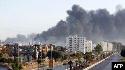 Une fumée noire se répand dans le ciel après l'incendie d'un dépôt pétrolier lors d'affrontements entre des milices rivales près de l'aéroport international de Tripoli, à la périphérie de la capitale, le 13 août 2014.