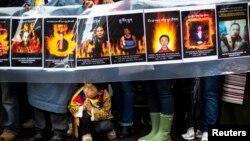 Những người biểu tình phản đối cầm ảnh của những người tự thiêu trong một cuộc tuần hành, bày tỏ tình đoàn kết, từ Lãnh sự quán Trung quốc đến trụ sở Liên hiệp quốc ở New York 10/12/12