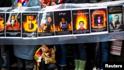A child gestures at the feet of protesters holding a sign commemorating victims of self-immolation during a solidarity march to the United Nations Headquarters in support of Tibet, New York, December 10, 2012.
