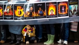 A child gestures at the feet of protesters holding a sign commemorating victims of self-immolation during a solidarity march from the Chinese Consulate to the United Nations (UN) Headquarters in support of Tibet in New York, December 10, 2012.