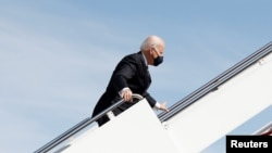 U.S. President Joe Biden grabs onto the railing after he stumbled while boarding Air Force One as he departs Washington on travel to Atlanta, Georgia to promote the $1.9 trillion coronavirus disease (COVID-19) aid package known as the American Rescue Plan