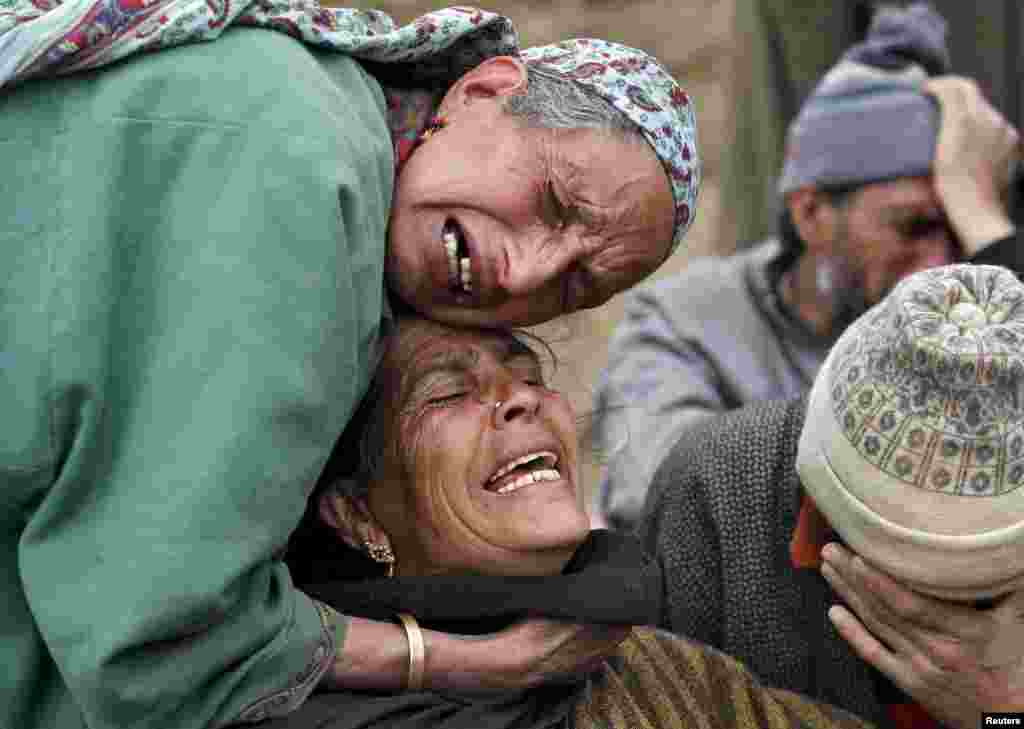 Relatives mourn during the funeral of the victims who died after a hillside collapsed onto a house at Ledhan village, west of Srinagar. Heavy rains and a landslide in the Himalayan region of Kashmir killed 17 people, police said as Indian authorities continued working to rescue stranded villagers, with unseasonal rains raising fears of flash floods in the mountainous north.