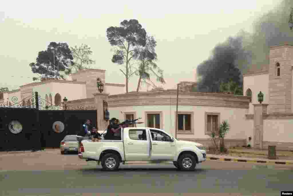 Armed men aim their weapons as smoke rises in the background near the General National Congress, in Tripoli, May 18, 2014.