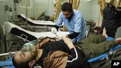 A wounded Palestinian lies in Al-Najar hospital after an Israeli air strike in Rafah in the southern Gaza Strip, April 8, 2011