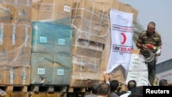 Palestinians unload Turkish aid shipments upon arrival in the Gaza Strip at Kerem Shalom crossing between Israel and southern Gaza Strip, July 4, 2016.