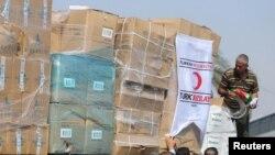Warga Palestina menurunkan bantuan kemanusiaan asal Turki setibanya di Jalur Gaza yaitu di Kerem Shalom, sebuah perlintasan antara Israel dan sisi selatan Jalur Gaza. (Foto: REUTERS/Ibraheem Abu Mustafa)