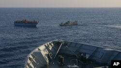 In this photo released by the Italian Navy on April 9, 2014, Italian Navy's dingies approach a boat carrying migrants along the Mediterranean sea, off the Sicilian island of Lampedusa