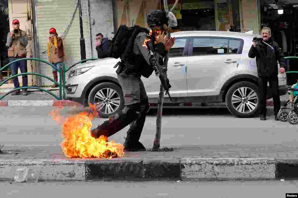 An Israeli border policeman is on fire as he is hit with a molotov cocktail thrown by Palestinian demonstrators during a protest against the U.S. President Donald Trump's Middle East peace plan, in Hebron in the Israeli-occupied West Bank, Feb. 3, 2020,