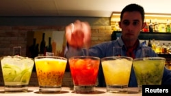 FILE - A barman prepares caipirinhas, Brazil's national cocktail, made with cachaca (sugar cane hard liquor), sugar and lemon or another fruit.