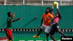 Fabrice Ondoa, gardien du Cameroun, à droite, subtilise une balle de la tête de Wilfried Bony de la Côte d'Ivoire lors du match de qualification pour la Coupe d'Afrique des Nations au stade Felix Houphouet Boigny à Abidjan, 19 novembre 2014.