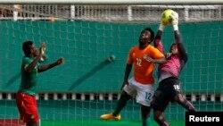 Fabrice Ondoa gardien du Cameroun, à droite, subtilise une balle de la tête de Wilfried Bony de la Côte d'Ivoire lors du match de qualification pour la Coupe d'Afrique des Nations au stade Félix Houphouet Boigny à Abidjan, 19 novembre 2014.