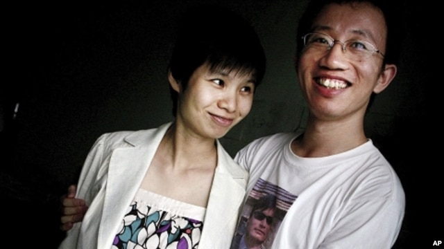 In this July 6, 2007 file photo, Hu Jia, right, and Zeng Jinyan, husband-and-wife activists, pose for a picture at their home in Beijing. Zeng said she visited Hu, who was jailed for sedition more than three years ago, in prison June 20, 2011. Jia was rel
