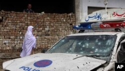 A Pakistani woman walks past a police vehicle hit by a roadside bombing in Charsadda near Peshawar, Pakistan, March 31, 2011
