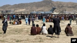 In this Aug. 16, 2021, file photo hundreds of people gather near a U.S. Air Force C-17 transport plane along the perimeter at the international airport in Kabul, Afghanistan. (AP Photo/Shekib Rahmani, File)