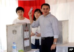"FILE - Jakarta Governor Basuki ""Ahok"" Tjahaja Purnama, who was seeking re-election, votes at a polling station during the runoff election in Jakarta, Indonesia, April 19, 2017. With him were his wife, Veronica; and son, Nicholas."