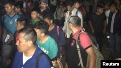 Central Americans are seen in the town of Tantima, Mexico, after Mexican authorities said that they rescued 147 Central Americans abandoned in the wilderness of Veracruz state, in this handout photograph released by the Mexican National Institute of Migration, July 30, 2017.