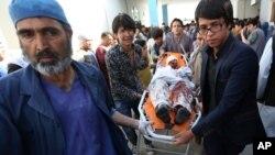 Petugas medis mengangkut korban luka-luka dalam ledakan bom kuat di Kabul hari Sabtu (23/7).