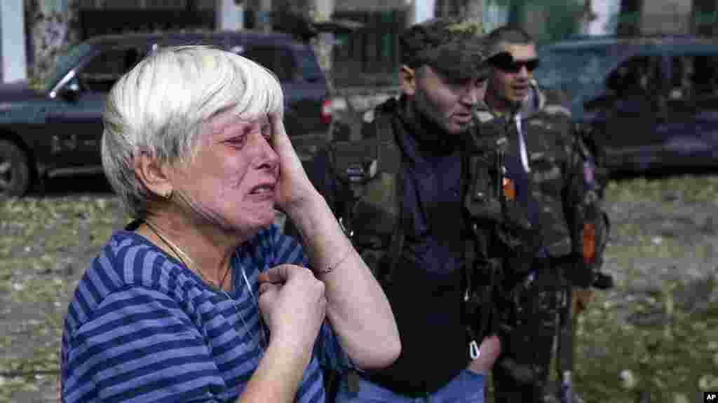 A local woman cries in front of a damaged school after shelling in the town of Donetsk, eastern Ukraine, Oct. 1, 2014.