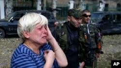 Một phụ nữ trong thị trấn Donetsk, miền đông Ukraine, khóc khi thấy một ngôi trường bị hư hại trong một vụ pháo kích 1/10/14