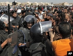 Anti-Mubarak protesters scuffle with riot police outside the Police Military Academy complex in Cairo, Egypt, August 3, 2011, during the trial session of ousted President Hosni Mubarak